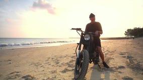 Μοτοσυκλετιστής που οδηγεί τη μοτοσικλέτα του στην παραλία κατά τη διάρκεια του ηλιοβασιλέματος κίνηση αργή φιλμ μικρού μήκους