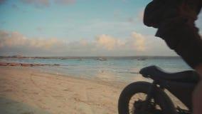 Μοτοσυκλετιστής που οδηγεί τη μοτοσικλέτα του στην παραλία κατά τη διάρκεια του ηλιοβασιλέματος κίνηση αργή απόθεμα βίντεο