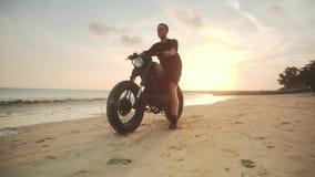 Μοτοσυκλετιστής που οδηγεί τη μοτοσικλέτα του στην παραλία κατά τη διάρκεια του ηλιοβασιλέματος απόθεμα βίντεο