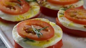 Μοτσαρέλα και ντομάτες σκηνή Φέτες του φρέσκου τυριού ντοματών και μοτσαρελών Σαλάτα με τη μοτσαρέλα και τις ντομάτες - απόθεμα βίντεο