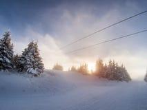 Μουντός ήλιος θανάτου σε μια κλίση σκι με τα χιονισμένα δέντρα στοκ φωτογραφία