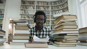 Μουσική ακούσματος ανδρών σπουδαστών χαμόγελου αφρικανική στο ακουστικό διαβάζοντας το βιβλίο φιλμ μικρού μήκους