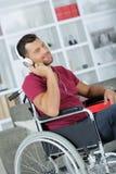 Μουσική ακούσματος ατόμων στα ακουστικά καθμένος στην αναπηρική καρέκλα Στοκ Φωτογραφίες