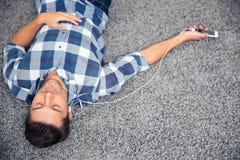 Μουσική ακούσματος ατόμων στα ακουστικά στο πάτωμα Στοκ φωτογραφίες με δικαίωμα ελεύθερης χρήσης