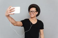 Μουσική ακούσματος ατόμων χαμόγελου η νέα ασιατική και κάνει selfie Στοκ Φωτογραφία