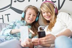 Μουσική ακούσματος αδελφών μέσω των ακουστικών στο σπίτι στοκ φωτογραφία