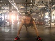 Μουσική ακούσματος γυναικών ικανότητας στα ασύρματα ακουστικά Να κάνει workout τις ασκήσεις στη γυμναστική Όμορφο αθλητικό κατάλλ στοκ εικόνες με δικαίωμα ελεύθερης χρήσης