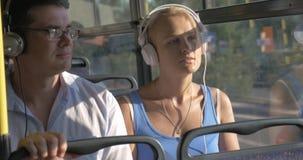 Μουσική ακούσματος γυναικών και ανδρών στην κάσκα κατά τη διάρκεια του ταξιδιού λεωφορείων απόθεμα βίντεο
