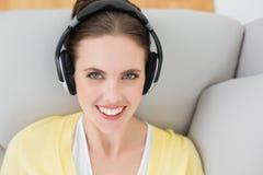 Μουσική ακούσματος γυναικών χαμόγελου μέσω των ακουστικών στον καναπέ Στοκ φωτογραφίες με δικαίωμα ελεύθερης χρήσης