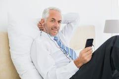 Μουσική ακούσματος επιχειρηματιών με το τηλέφωνό του στο κρεβάτι στοκ εικόνες