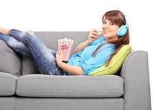 Μουσική ακούσματος κοριτσιών και κατανάλωση popcorn στον καναπέ Στοκ φωτογραφία με δικαίωμα ελεύθερης χρήσης