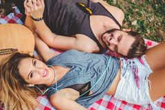 Μουσική ακούσματος κοριτσιών και κράτημα των χεριών με το φίλο Στοκ εικόνα με δικαίωμα ελεύθερης χρήσης