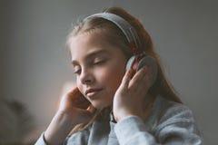 Μουσική ακούσματος κοριτσιών παιδιών στα ακουστικά με τις προσοχές ιδιαίτερες Στοκ Φωτογραφίες