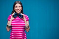 Μουσική ακούσματος κοριτσιών χαμόγελου με τα ακουστικά Στοκ Φωτογραφίες