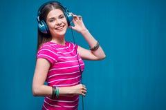 Μουσική ακούσματος κοριτσιών χαμόγελου με τα ακουστικά Στοκ Εικόνες