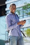 Μουσική ακούσματος νεαρών άνδρων στο τηλέφωνο κυττάρων του Στοκ εικόνα με δικαίωμα ελεύθερης χρήσης