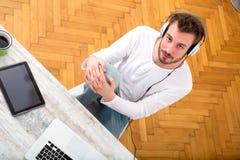 Μουσική ακούσματος νεαρών άνδρων στο lap-top του Στοκ φωτογραφία με δικαίωμα ελεύθερης χρήσης