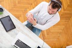 Μουσική ακούσματος νεαρών άνδρων στο lap-top του Στοκ φωτογραφίες με δικαίωμα ελεύθερης χρήσης