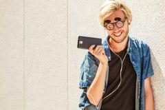 Μουσική ακούσματος χαμόγελου ατόμων Hipster μέσω των ακουστικών Στοκ Εικόνες