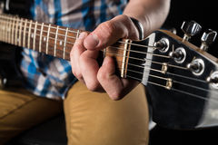 Μουσική και τέχνη Ηλεκτρική κιθάρα στα χέρια ενός κιθαρίστα, σε ένα απομονωμένο ο Μαύρος υπόβαθρο παιχνίδι κιθάρων Οριζόντιο πλαί στοκ εικόνα