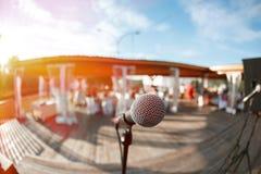 Μουσική στο πάρκο, μικρόφωνο με το ξύλινο υπόβαθρο σκηνών στοκ εικόνα με δικαίωμα ελεύθερης χρήσης