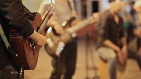 Μουσικοί οδών με τις κιθάρες που παίζουν για τους ανθρώπους απόθεμα βίντεο