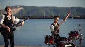 Μουσικοί που παίζουν τα τύμπανα και την κιθάρα κατά τη διάρκεια της υπαίθριας απόδοσης ζωνών απόθεμα βίντεο
