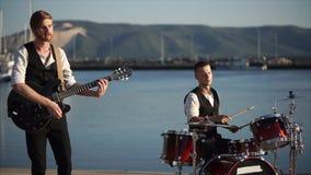 Μουσικοί που παίζουν τα τύμπανα και την κιθάρα κατά τη διάρκεια της υπαίθριας απόδοσης ζωνών φιλμ μικρού μήκους