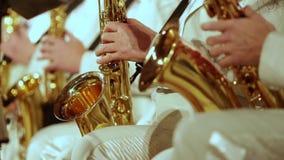 Μουσικοί στο άσπρο παιχνίδι κοστουμιών saxophones σε μια ζώνη τζαζ Μικρό DOF απόθεμα βίντεο