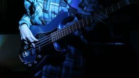Μουσικός βράχου που παίζει τη βαθιά κιθάρα στη συναυλία απόθεμα βίντεο