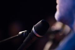 Μουσικός και μικρόφωνο στην βράχος-συναυλία, οριζόντια στοκ φωτογραφία