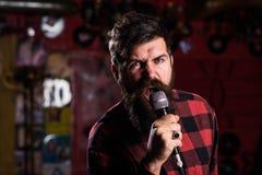 Μουσικός με τη γενειάδα και mustache τραγούδι τραγουδιού στο καραόκε Στοκ Εικόνες