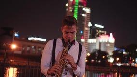 Μουσικός οδών που παίζει το saxophone στην προκυμαία στο υπόβαθρο της πόλης νύχτας Όμορφα φω'τα νύχτας απόθεμα βίντεο