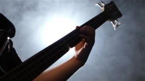 Μουσικός παιχνιδιού στη βαθιά κιθάρα τεσσάρων σειρών closeup κίνηση αργή απόθεμα βίντεο