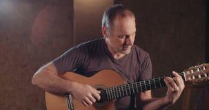 Μουσικός που παίζει την ακουστική κιθάρα σε ένα στούντιο καταγραφής απόθεμα βίντεο