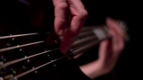 Μουσικός που παίζει την ηλεκτρική βαθιά μακροεντολή κιθάρων πέντε σειράς φιλμ μικρού μήκους