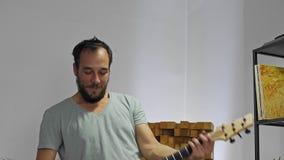 Μουσικός που παίζει την ηλεκτρική κιθάρα στο στούντιο εγχώριας μουσικής απόθεμα βίντεο