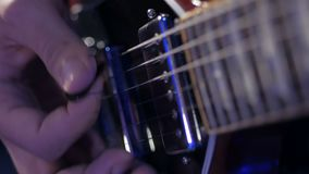 Μουσικός που παίζει την ηλεκτρική μελωδία κιθάρων Λεπτομέρειες των σειρών και δεξιού του κοντινού οι επαναλείψεις απόθεμα βίντεο