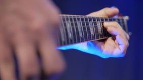 Μουσικός που παίζει την ηλεκτρική μελωδία κιθάρων Λεπτομέρειες των σειρών και δεξιού του κοντινού οι επαναλείψεις φιλμ μικρού μήκους