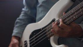 Μουσικός που παίζει τη βαθιά κιθάρα με την επιλογή στο στούντιο απόθεμα βίντεο