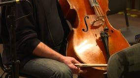 Μουσικός που προετοιμάζει το violancello για να παίξει στην ορχήστρα φιλμ μικρού μήκους