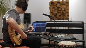 Μουσικός που συνδέει στην ηλεκτρική κιθάρα στο στούντιο εγχώριας μουσικής απόθεμα βίντεο