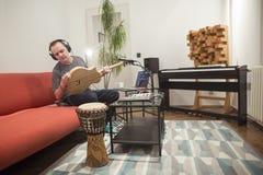 Μουσικός που συνδέει στην ηλεκτρική κιθάρα στο στούντιο εγχώριας μουσικής στοκ εικόνες
