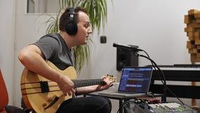 Μουσικός που τραγουδά και που παίζει την ηλεκτρική κιθάρα στο στούντιο εγχώριας μουσικής απόθεμα βίντεο