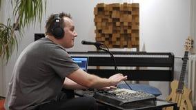 Μουσικός που τραγουδά και που παίζει το πληκτρολόγιο του Midi στο στούντιο εγχώριας μουσικής απόθεμα βίντεο