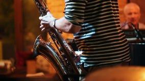 Μουσικός σε μια ριγωτή μπλούζα που παίζει το saxophone για μια απόδοση σε έναν φραγμό τζαζ απόθεμα βίντεο