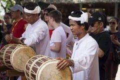 Μουσικός στα άσπρα ενδύματα που παίζει στο παραδοσιακό τύμπανο Στοκ Φωτογραφίες