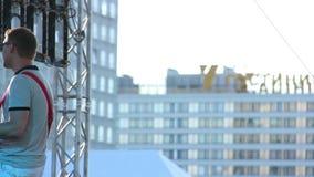 Μουσικός στα γυαλιά που παίζει την κιθάρα στο υπόβαθρο των κτηρίων απόθεμα βίντεο