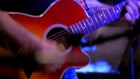 Μουσικός στη συναυλία βράχου - οι κιθαρίστες παίζουν την κόκκινη ακουστική κιθάρα στη λέσχη νύχτας, κλείνουν επάνω απόθεμα βίντεο