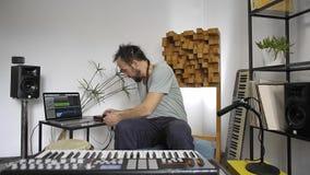 Μουσικός στο στούντιο εγχώριας μουσικής που συνδέει το μικρόφωνο μέσα και που εξετάζει απόθεμα βίντεο